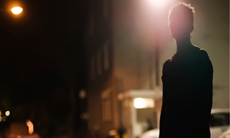 Silhouette of a woman on a street corner at night