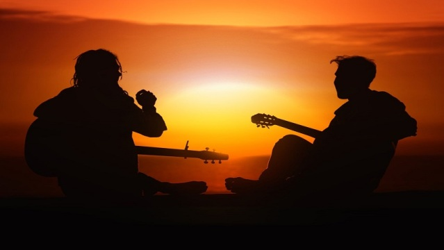 two-friends-silhouette-playing-guitar-music-at-sunset